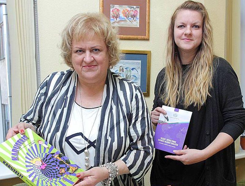 """Latviešu valodas aģentūras direktora vietniece Dace Dalbiņa (no kreisās) un diasporas projektu koordinatore Aija Otomere rāda diasporas skoliņām sūtāmās grāmatas, kuru vidū ir arī """"LA"""" apgādā izdotais Ulda Ausekļa dzejoļu krājums."""