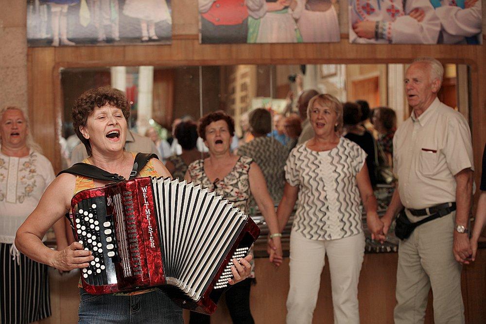 """Omskas Latviešu biedrības ļaudis ciemiņus sagaidīja ar dziesmu """"Šeit ir Latvija"""". Priekšplānā folkloras ansambļa """"Daina"""" vadītāja Raja Bakanova."""
