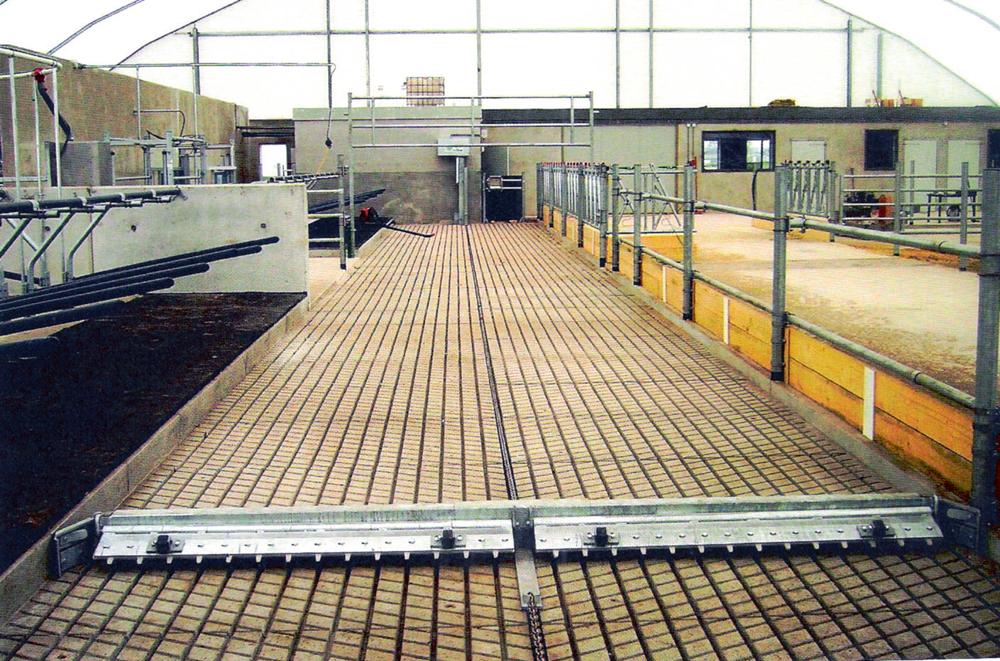 """Mēslu eja ar dziļi rievotu grīdu. Tās tīrīšanai izmantojams Nīderlandes firmas """"JOZ"""" demostrētais platskrēperis, kura skrāpim ir pievienoti rievu tīrīšanas pirksti"""
