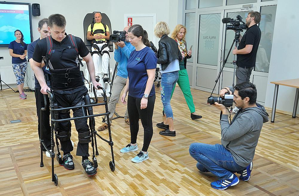 """Artis Salenieks pirms trim gadiem cieta autoavārijā un zaudēja spēju staigāt. Kaut arī robottehnoloģija negarantē iespēju atkal nostāties uz savām kājām, nevarēja nepamanīt viņa prieku spert soļus, izmēģinot """"Ekso Bionic"""". Kaut vai ar robota palīdzību. """"Patīkami, ka var izlocīt kājas. Jāmēģina iekustināt muskuļus – jāliek viņiem strādāt. Jāmēģina iedarbināt impulsus, varbūt smadzenes atcerēsies, kā tas notiek. Pats soļus nevaru veikt, taču svaru uz kājām jūtu,"""" teica Artis."""