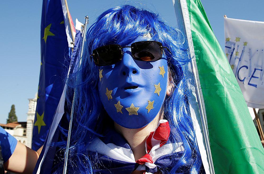 Demonstrants ES krāsu sejas maskā ar Britānijas un Itālijas karogiem pirms Apvienotās Karalistes premjerministres Terēzas Mejas runas Florencē atgādina, ka breksits grauj kā britu, tā eiropiešu cerības.