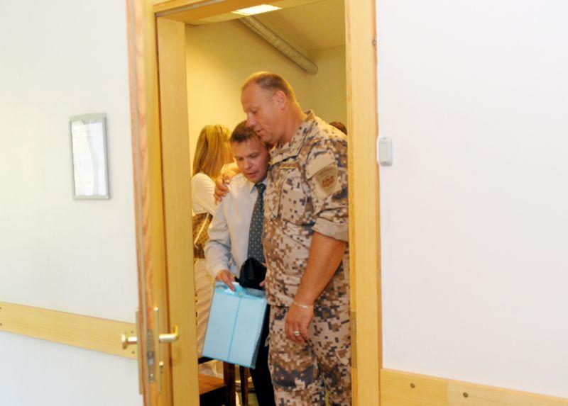 Toreizējais Nacionālo bruņoto spēku dižkareivis (tagad aizsardzības ministrs) Raimonds Bergmanis (no labās) atbalsta atvaļināto NBS karavīru Vladimiru Bakuļinu pirms tiesas sēdes Latgales priekšpilsētas tiesā 2010. gada augustā.