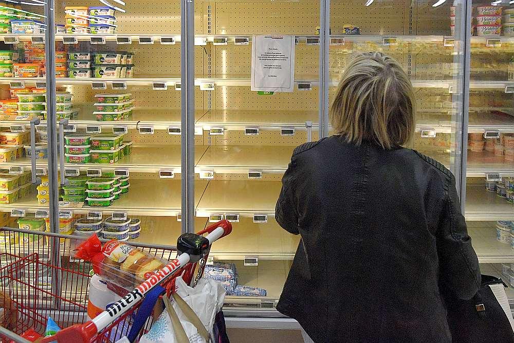 """Pircēja lasa paziņojumu pie lielveikala ledusskapja plaukta Rezē, Francijas rietumos – """"Sakarā ar izejvielu trūkumu sviesta izgatavošanai mēs nevaram jums piegādāt un pārdot šo produktu""""."""