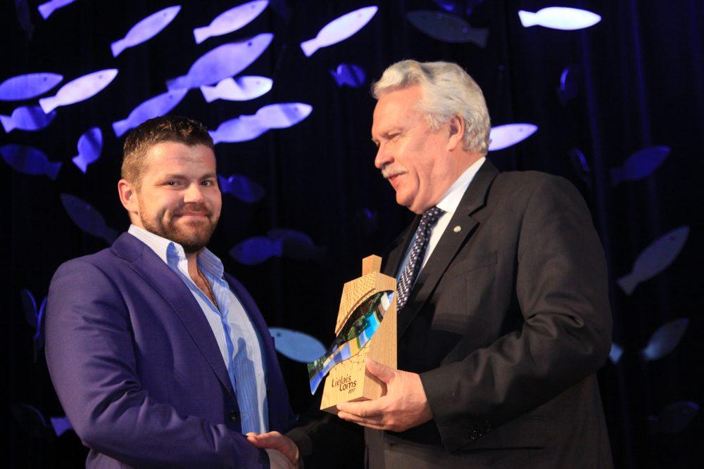 """Apsveikumus no ministra saņem SIA """"BraDava"""" pārstāvis Aleksejs Blohins."""