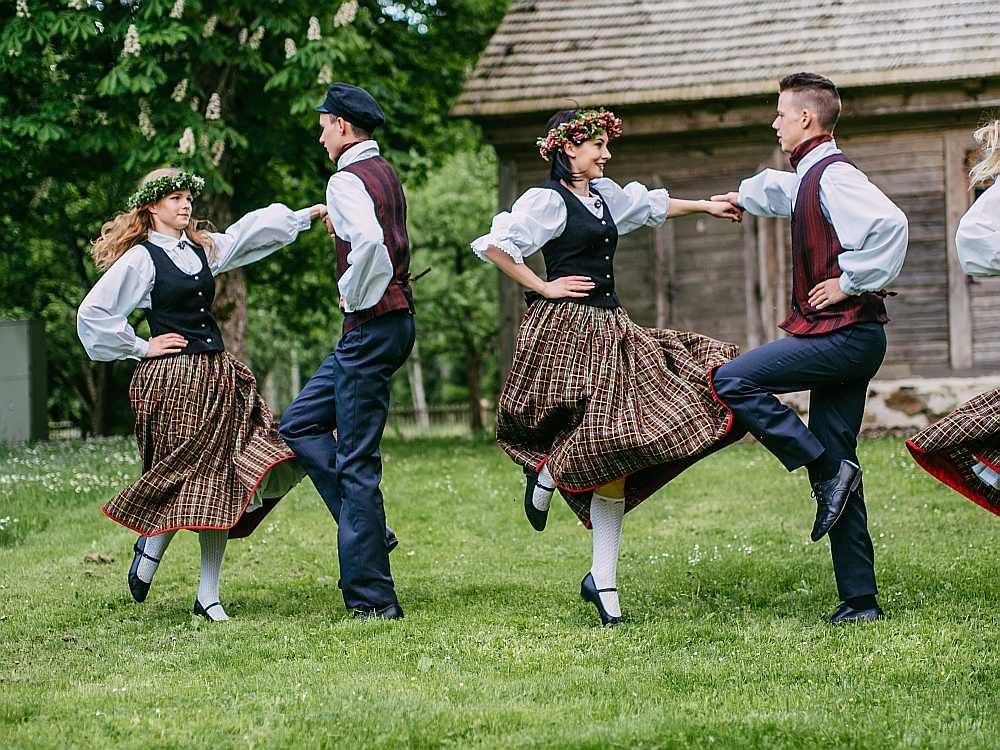 """Dundagas kultūras pils jauniešu deju kolektīva """"Dun-dang"""" dejotāju pāri šovasar Kubalu skolā-muzejā dejo Ziemeļkurzemes tautastērpos."""