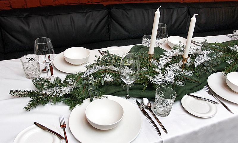 Mežs ienāk mājā. Šajā galda klājumā uzsvars likts uz kompozīciju, kas veidota no mūžzaļo augu– egles, priedes un tūjas – zariem. Izmantoti arī eikalipta zari (tos var nopirkt ziedu veikalos), kas simbolizē pārticību. Košumam – mākslīgās spalvas baltā krāsā. Lai kompozīcija no dabīgajiem materiāliem nenotraipītu balto galdautu, tā kārtota uz tumšzaļa sakrokota auduma.  Ziemassvētkos neiztikt bez svecēm! Šajā gadījumā izmantoti dažāda augstuma svečturi ar garām baltām svecēm. Tos nevajadzētu likt vienā rindā kā kareivjus ierindā, bet grupēt pa pāriem.