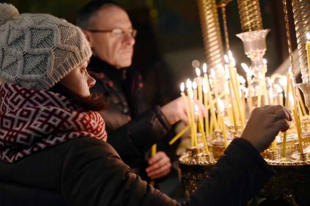 Cilvēki noliek sveces Ziemassvētku dievkalpojuma laikā.
