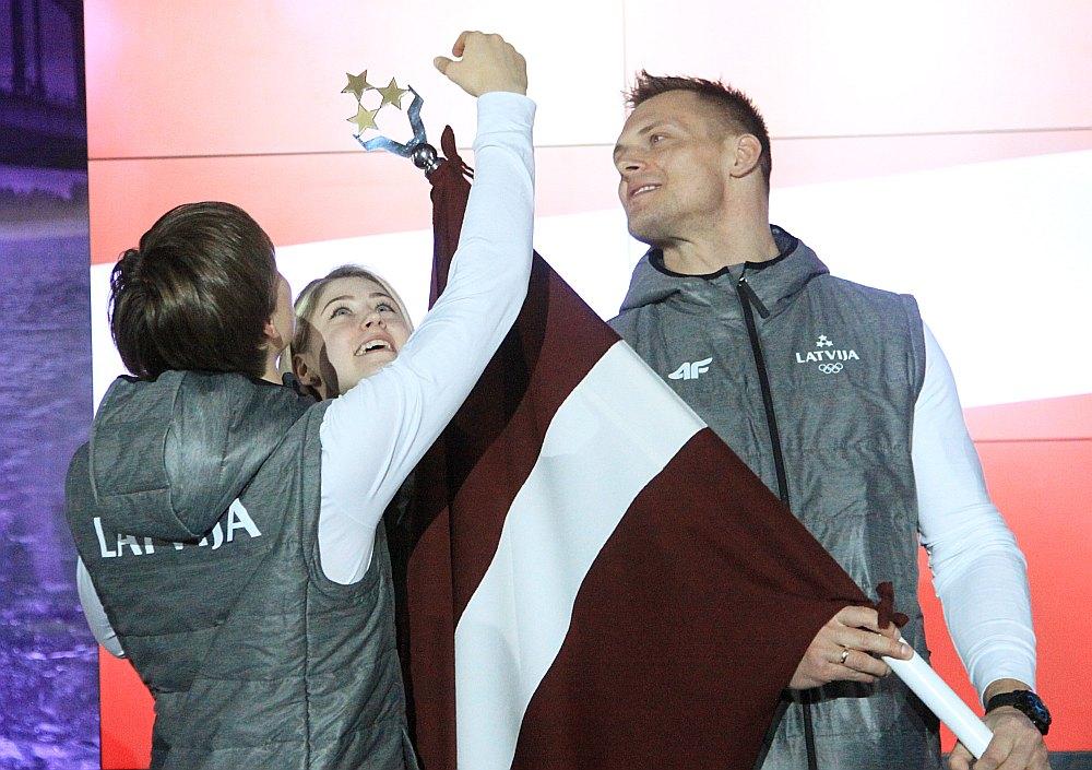 Karogam, kas Phjončhanas spēļu atklāšanas parādē būs Daumanta Dreiškena spēcīgajās rokās, pieskarties vēlējās arī mūsu olimpiskie daiļslidotāji Deniss Vasiļjevs un Diāna Ņikitina.