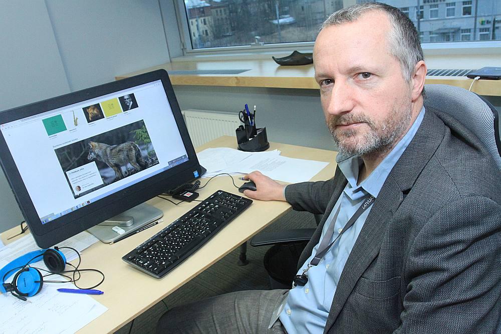 """Nacionālās enciklopēdijas galvenais redaktors Valters Ščerbinskis demonstrē, kāda izskatīsies enciklopēdijas elektroniskā versija: """"Jo Nacionālā enciklopēdija jau sēž it kā uz diviem krēsliem – viens ir drukātā, otrs – elektroniskā versija, kas ir pamatu pamats."""""""