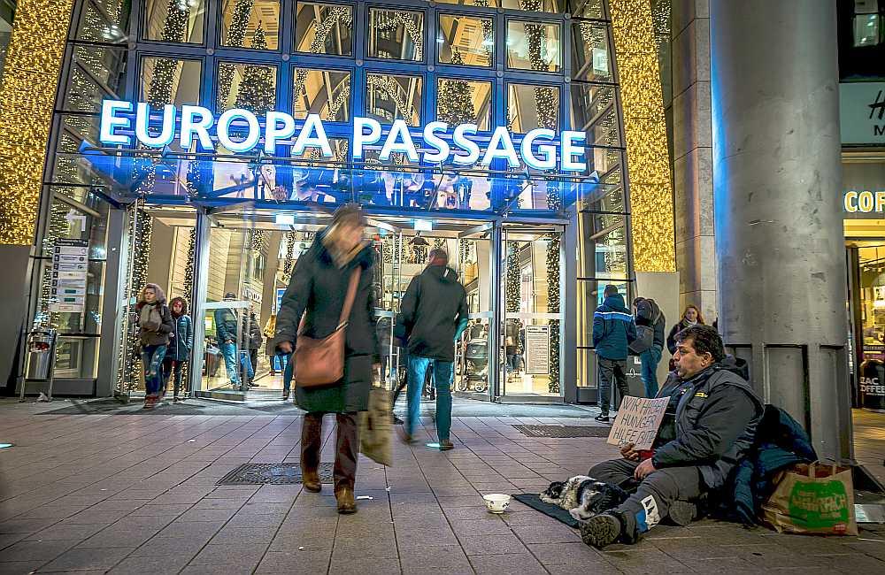 """Bezpajumtnieks iepirkšanās centra """"Europa Passage"""" priekšā Hamburgā Vācijā gadu mijā."""