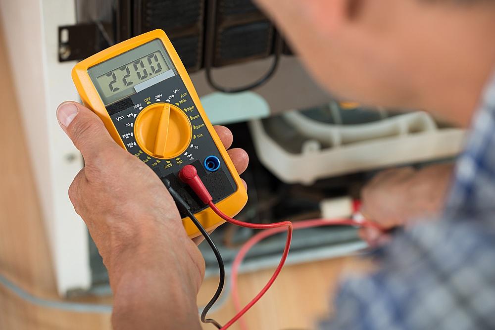 Elektriķis pārbauda spriegumu kontakligzdā.