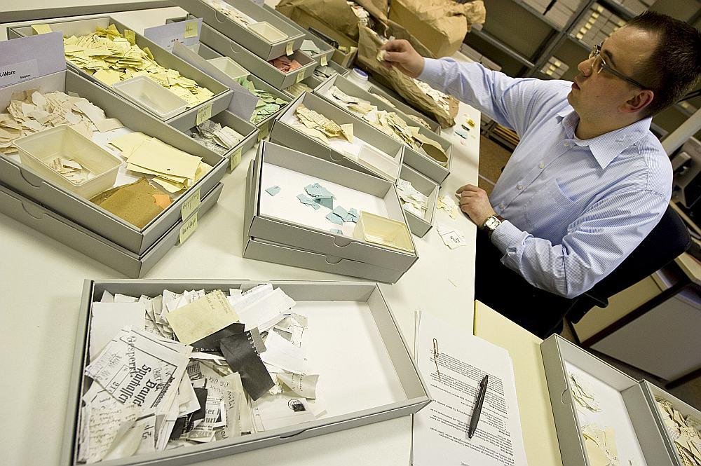 """""""Stasi"""" dokumentus jau vairākus gadus restaurē, ar rokām pēc puzles principa savietojot saplēsto papīru strēmeles."""