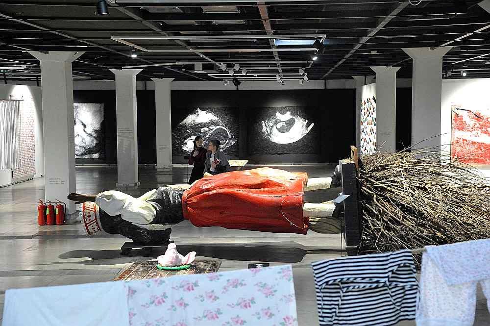 """Aigars Bikše, """"LIBAU – HALIFAX – LIBAU"""". Putuplasts, stikla šķiedra, emaljas krāsa, tērauda armējums, saknes, zari. 170x400x765 cm. 2015. Autora koncepcijā Milda – melnādaina latviešu tautumeita – atgriezusies Latvijā pēc vairāk nekā 100 gadiem, ko viņas dzimta pavadījusi trimdā, aicinot meklēt, cik tālu aizsniedzas mūsu, latviešu, saknes."""