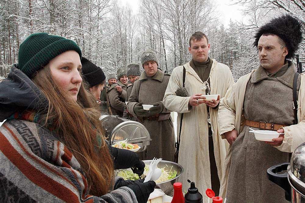 Ziemassvētku kauju ainu dalībnieki pusdieno lauka virtuvē.