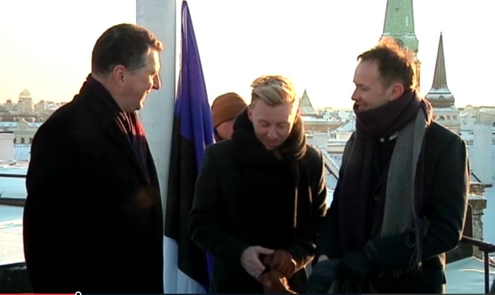 Rīgas pils tornī mūziķis Renārs Kaupers kopā ar Valsts prezidentu Raimondu Vējoni uzvelk mastā kaimiņvalsts karogu.