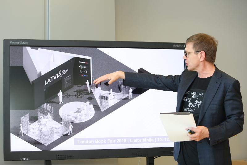 Latvijas Investīciju un attīstības aģentūras direktors Andris Ozols demonstrē plānoto Latvijas stendu Londonas grāmatu tirgū.