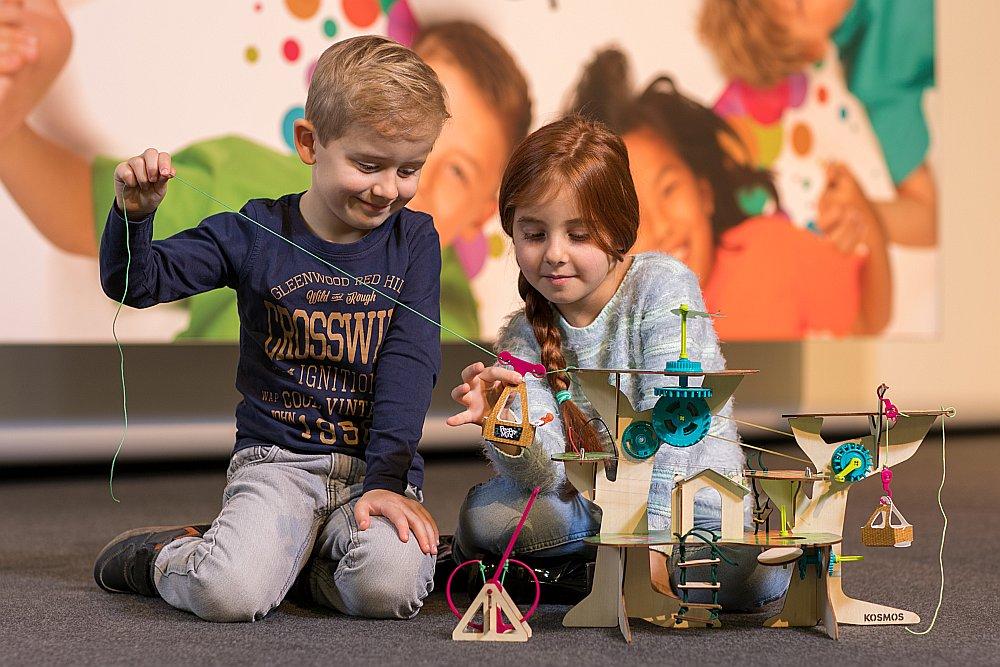 """Bērni izstādē """"Spielwarenmesse"""" aizrāvušies ar īpašu koka māju, kas skolēnu kategorijā atzīta par labāko rotaļlietu."""