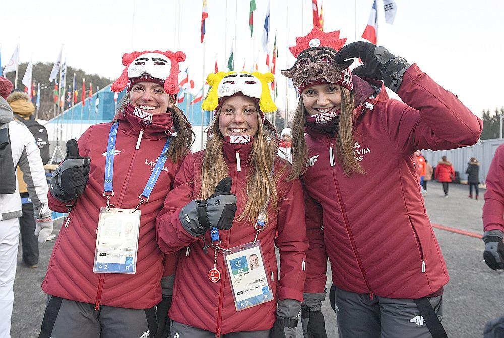 Latvijas kamaniņu sportiste Ulla Zirne (no labās), distanču slēpotājas Patrīcija Eiduka un Inga Paškovska pēc Latvijas karoga pacelšanas ceremonijas olimpiskajā ciematā.