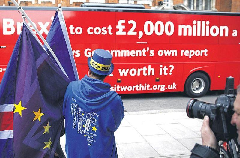 """Sarkanais antibreksita autobuss, uz kura rakstīts """"Breksits izmaksās 2000 miljonus nedēļā… teikts valdības ziņojumā"""", un tālāk seko jautājums – """"Vai tas ir tā vērts""""? Sākumā kampaņas organizators apmulsa, taču pēc BBC žurnālista komentāra, ka laikam trim Džeikobiem patīk autobuss un lai jau danco, intervija turpinājās."""