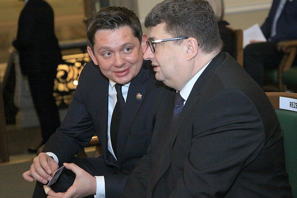 Saeimas deputāts Artuss Kaimiņš (no kreisās) pirms parlamenta balsojuma aprunājas ar SAB vadītāju Jāni Maizīti.