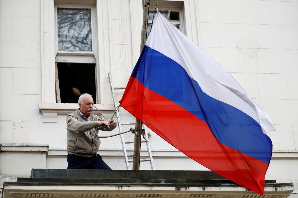 Kāds vīrietis noņem karogu pie Krievijas vēstniecības Londonā, Lielbritānijā, 14.03.2018.