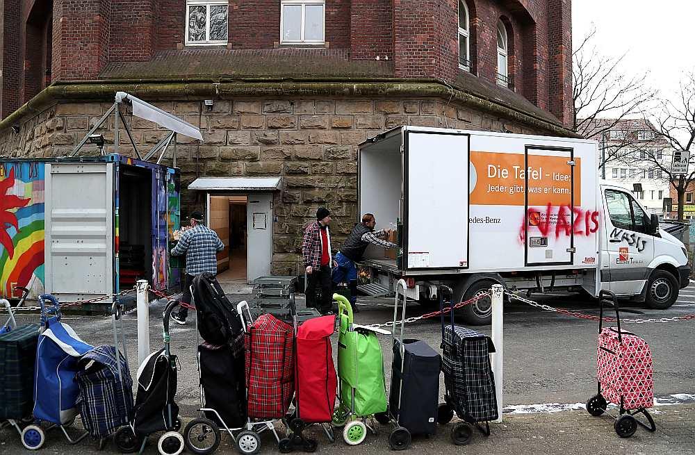 """Naktī uz 26. februāri Esenes """"Tafel"""" ieejas durvis un sešus pie ēkas esošos pārtikas transportēšanas furgonus vandaļi apkrāsoja ar nacistiskiem saukļiem."""