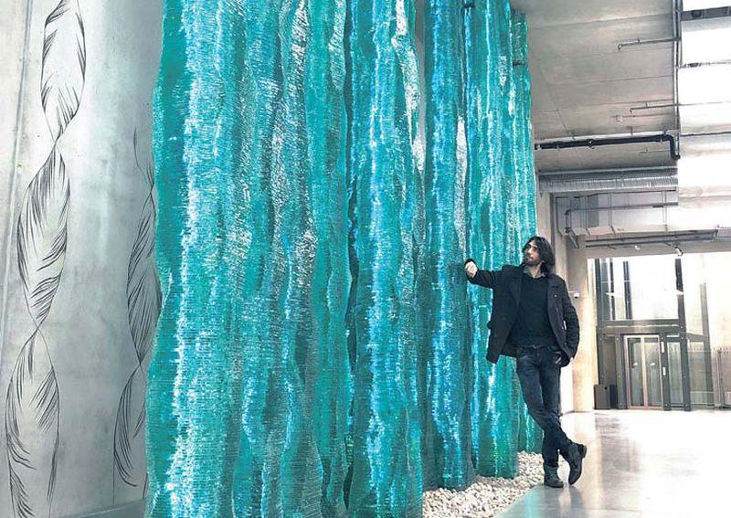 """Ernests Vītiņš pie lielākā laikmetīgās stikla mākslas darba Baltijā – """"Dabā"""" Latvijas Universitātes Dabaszinātņu akadēmiskajā centrā."""