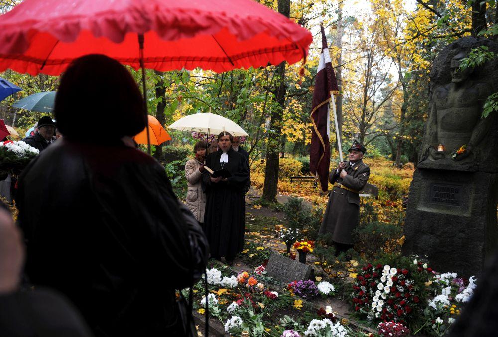 Mācītājs Guntis Kalme uzrunā klātesošos Meža kapos pie pretpadomju aktīvista Gunāra Astras atdusas vietas, kur notiek atceres brīdis. 2011. gada 22. oktobrī