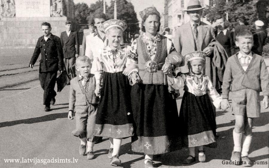 1948. gada 21. jūlijs. Ģimene nāk no dziesmu svētkiem Esplanādē. Fotogrāfijas centrā Frīda Puzule, kura darinājusi tautas tērpu ne tikai sev, bet arī saviem bērniem un radu bērniem. No kreisās: Jānis Pladers, Inta Kalniņa, Frīda Puzule, Ieva Puzule, Andris Puzulis.