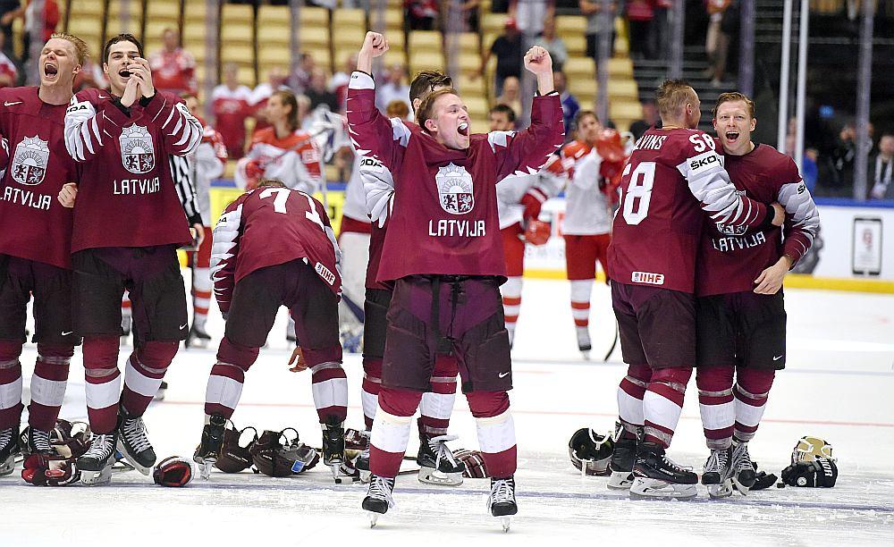 Latvijas hokeja izlases spēlētāji līksmo pēc uzvaras pār Dānijas komandu.