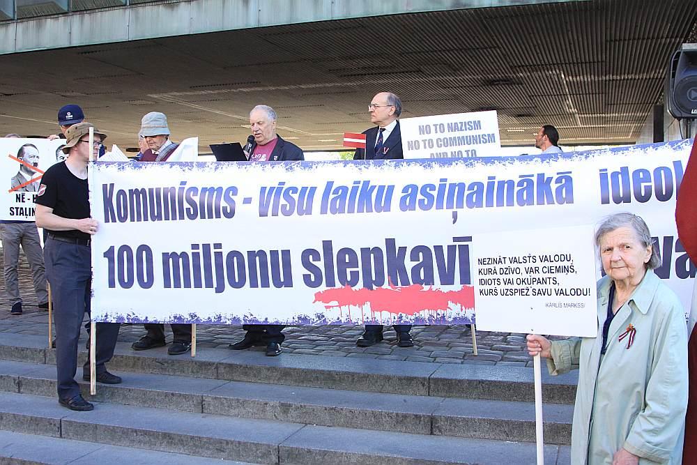 Pie Okupācijas muzeja uz protesta akciju pulcējās ap 50 represēto un viņu domubiedru. Pasākuma dalībnieki turēja Latvijas karogus ar sēru noformējumu un plakātus, kuros pausts nosodījums gan komunismam, gan nacismam.