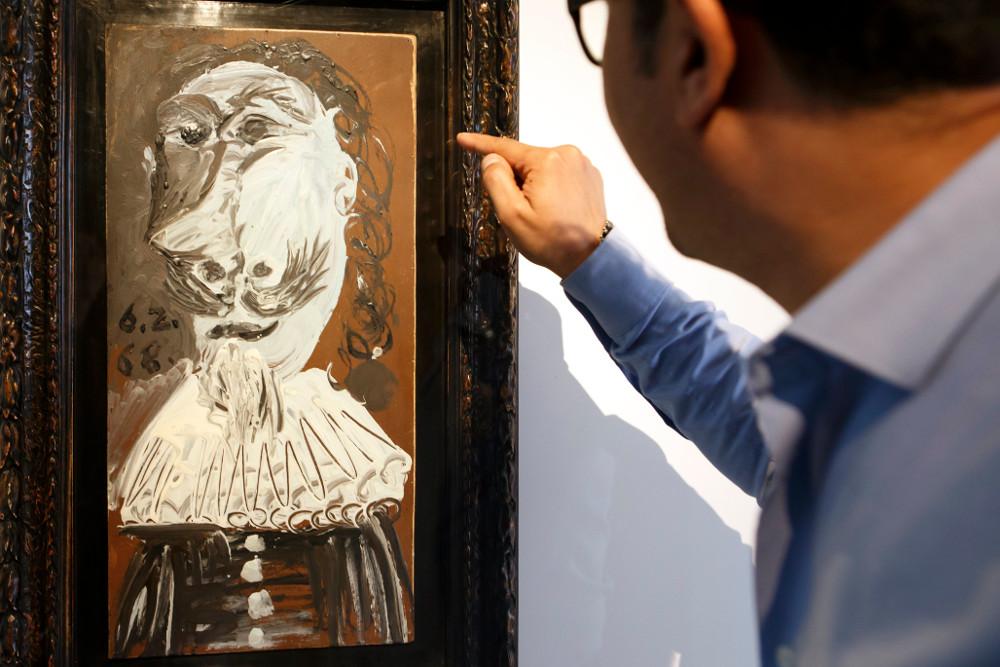 """Apmeklētājs Ženēvas Laikmetīgās mākslas muzejā (MAMCO) apskata Pablo Pikaso gleznu """"Musketiera biste""""."""