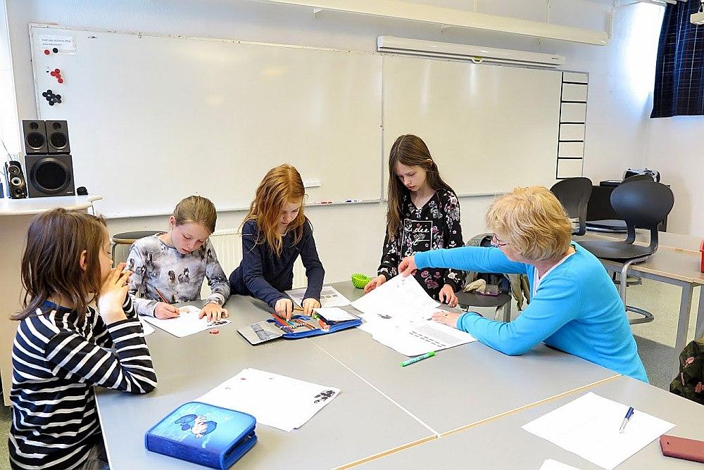 Raksta autore – skolotāja Gunta Neimane – latviešu valodas nodarbībā, kurā mācās Artis (no kreisās) Emīlija, Adriana un Keita.