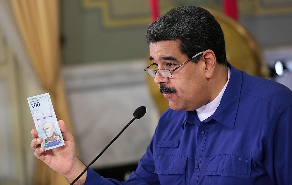Venecuēlas prezidents Nikolass Maduro demonstrē jauno banknoti.
