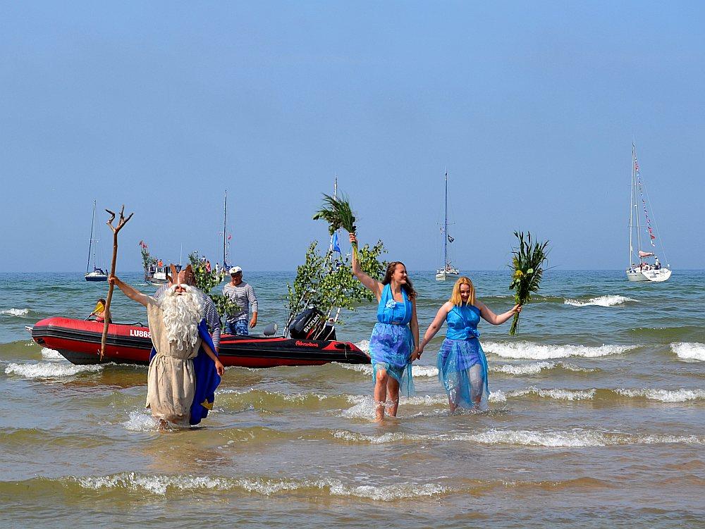 """Pāvilostā no jūras ar laivu ieradās Neptūns un nāriņas, kas visus sveica svētkos un arī vadīja zvejnieku sporta spēles: zābaka mešanu mērķī atmuguriski, virves un laivas vilkšanu. Kā teica Neptūns: """"Izbaudiet Pāvilostas piekrastes jūru – ūdens tajā ir par velti!"""""""