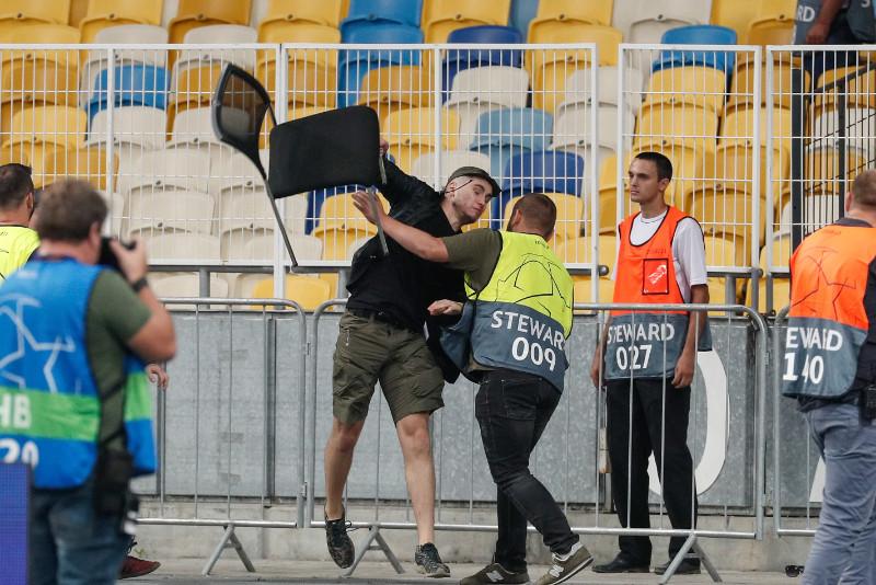 """Kijevas """"Dinamo"""" fans met krēslu pretinieku līdzjutēju virzienā."""