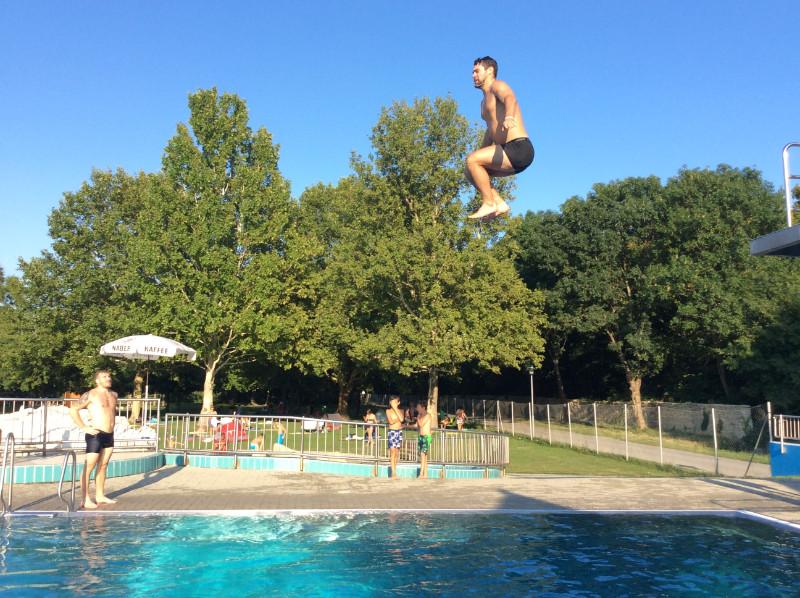 Kaspars Daugaviņš lec baseinā no tramplīna.