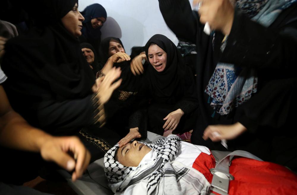 Nogalinātā palestīniešu pusaudža Belala Halifa  tuvinieces sēro pie viņa zārka.