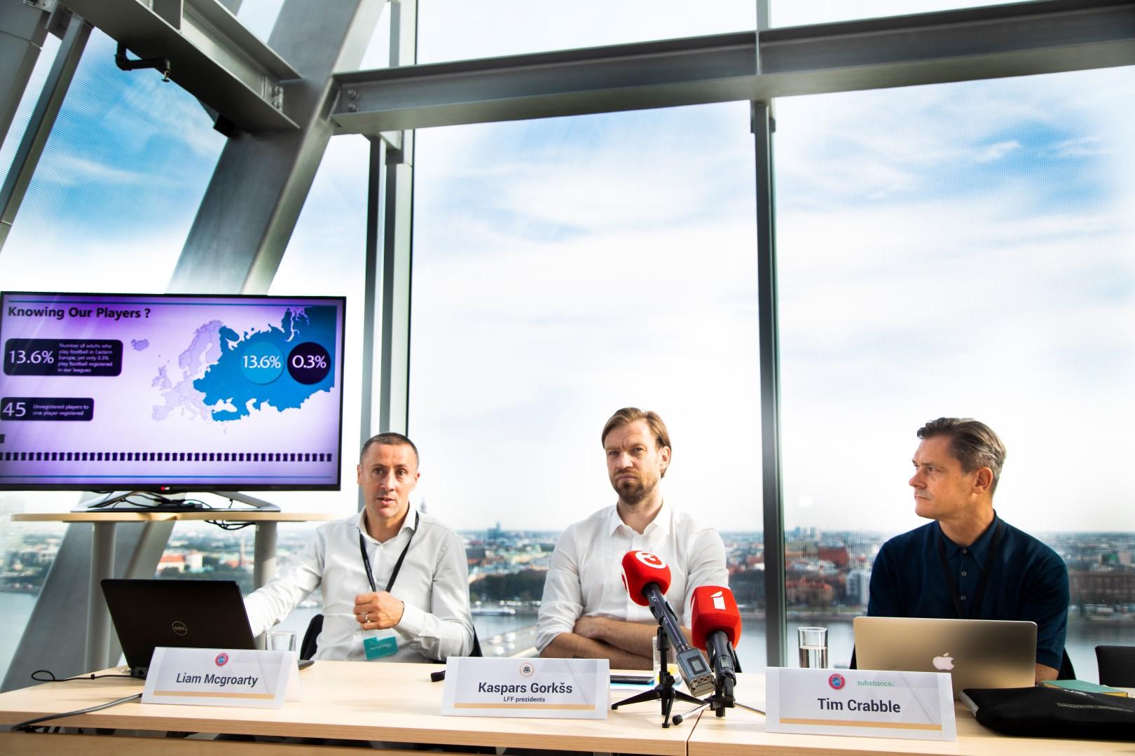 UEFA pārstāvji Liams Makgroartijs (pa kreisi) un Tims Krabls (pa labi) asistējot Kasparam Gorkšam vēsta par futbola un ekonomikas kopsakarībām.