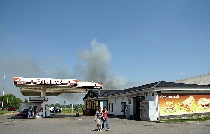"""Noliktavu ēku ugunsgrēka dūmi virs degvielas uzpildes stacijas """"Dinaz"""" Hanzas ielā."""