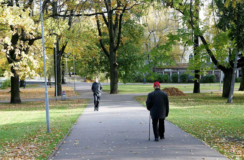 Cilvēki rudenī Kronvalda parkā.