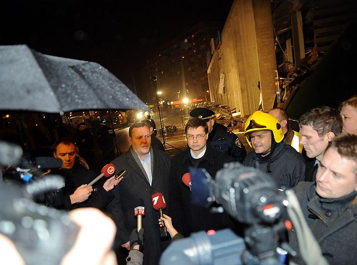"""Iekšlietu ministrs Rihards Kozlovskis (no kreisās) un Ministru prezidents Valdis Dombrovskis  2013/gada 22.novembrī atbild uz žurnālistu jautājumiem pie veikala """"Maxima"""" Zolitūdes mikrorajonā kur iebrucis jumts, kā rezultātā gājuši bojā un cietuši cilvēki."""