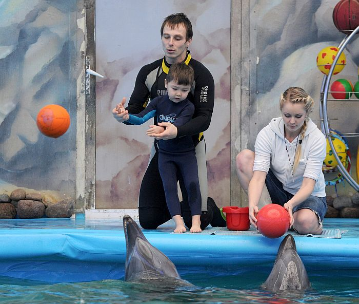 A pedagogue-diver assists an autistic child during a dolphin therapy session at the cultural and health center Nemo in the Belarus capital Minsk, on December 3, 2012.   AFP PHOTO / VIKTOR DRACHEV