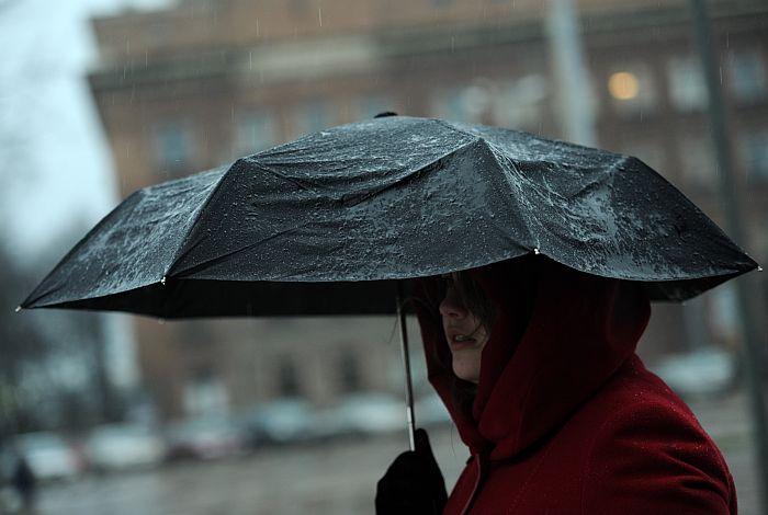 Sieviete ar lietussargu lietus un krusas laikā pilsētā.