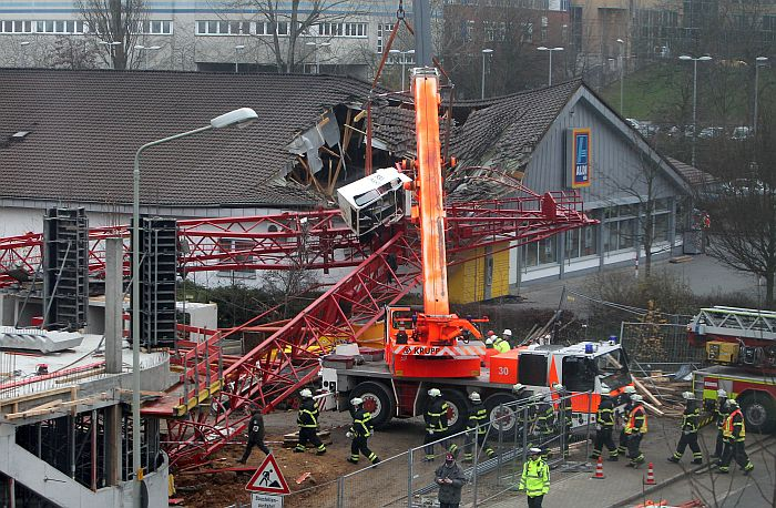 Rescuers gather near a crane that crashed down and partially distroyed the roof of a discount supermarket Aldi in Bad Homburg, western Germany, on December 11, 2013. One person was killed and five others injured when the crane fell onto the supermarket. AFP PHOTO / DANIEL ROLAND