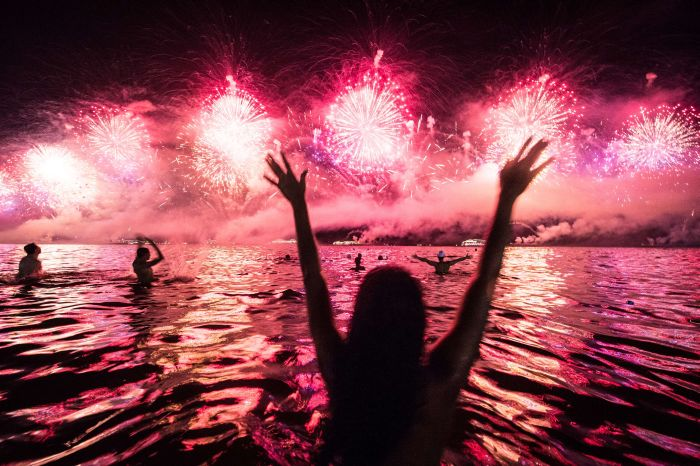 Cilvēki sajūsmā par Jaungada uguņošanu Riodežaneiro Kopakabana pludmalē 2014. gads AFP PHOTO / YASUYOSHI CHIBA