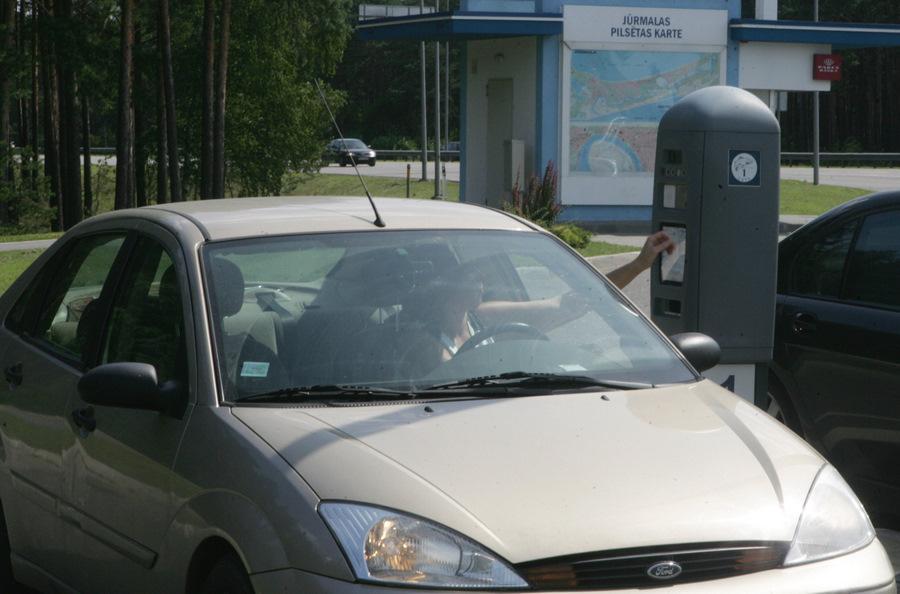 Sieviete iegādājas autotransporta caurlaidi iebraukšanai Jūrmalas pilsētas īpaša režīma zonā kontrolpunktā Priedainē pirms iebraukšanas pilsētā.