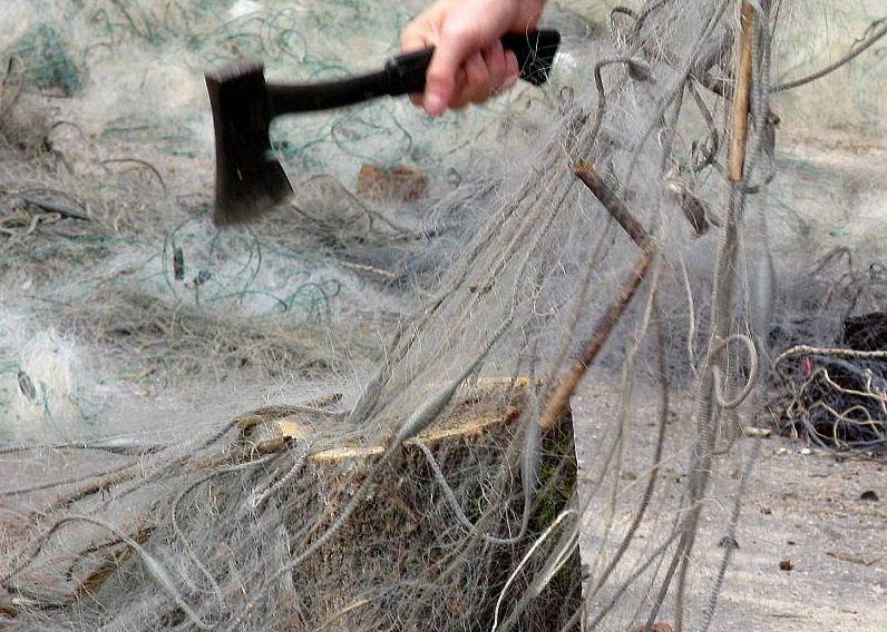 No ūdens izņemtie nelegālie tīkli tiek iznīcināti sacērtot.