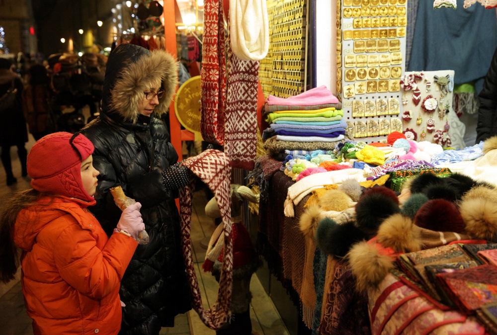 Cilvēki iepērkas amatnieku Ziemassvētku tirdziņā Līvu laukumā.