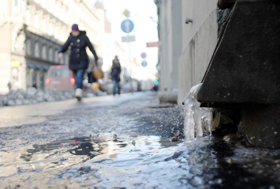 Gājēji un ledus uz ietves pie notekas.